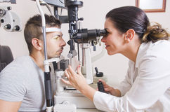 Optical lab, professional woman. Young boy in an optical scans machine exams his vision and optometry Stock Images