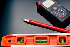Optical level, laser range finder and a pencil lying on the floor Stock Photography