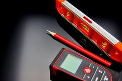 Optical level, laser range finder and a pencil lying on the floor Royalty Free Stock Photos