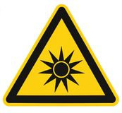 Optical radiation hazard caution safety danger warning text sign sticker label, artificial light beam icon symbol, isolated black. Triangle over yellow, large Stock Photos