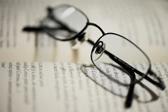 Optical reading glasses. Optical glasses for reading on the open book Royalty Free Stock Photo