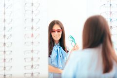 Woman Trying on Many Eyeglasses Looking in the Mirror stock photography