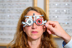 Optican checking eyes of woman for new glasses Royalty Free Stock Photography