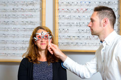 Optican checking eyes of woman for new glasses Stock Photo