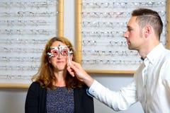Optican, das Augen der Frau auf neuen Gläsern überprüft Stockfoto