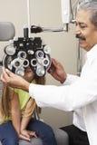 Optician в хирургии давая испытание глаза девушки Стоковое Фото