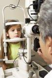 Optician в хирургии давая испытание глаза девушки Стоковые Изображения RF