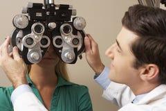 Optician в хирургии давая испытание глаза женщины Стоковая Фотография