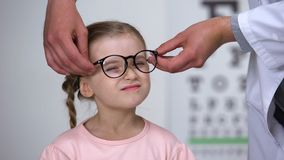 Optician кладя стекла на маленькую девочку и делая ее счастливую, профессиональную помощь акции видеоматериалы