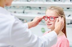 Optician кладя стекла к девушке на магазине оптики стоковое фото