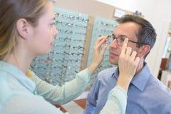 Optician помогая клиенту стоковое фото