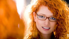 At optician. Young attractive girl wearing glasses looking at a mirror. At the optician Royalty Free Stock Photos