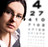 At the optician. Beautiful young woman wears trendy glasses stock photography