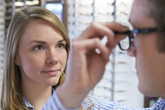Optician Advising Client On Choice Of Glasses Royalty Free Stock Photography