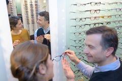 Optician advising female client. Optician stock images