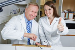 Optician apprentice holding thumbs Royalty Free Stock Photo