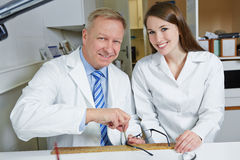 Optician and apprentice in workshop Royalty Free Stock Image