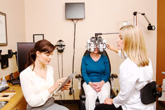 Optician checking with employee for needed info Royalty Free Stock Photos
