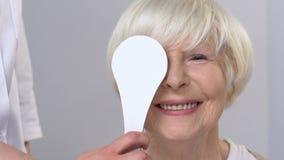 Optician closing elderly woman eye, checking vision, clinical examination. Stock footage stock video