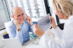 Optician consulting customer about frames Stock Image