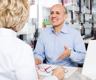Optician consulting customer about frames Royalty Free Stock Photos