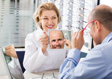 Optician consulting customer about frames Royalty Free Stock Photography