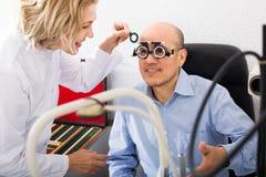 Optician doing eye check up. Senior women optician doing eye check up to elderly smiling man stock photography