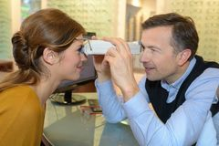 Optician examines eyesight pretty client Royalty Free Stock Photo