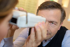 Optician examines eyesight pretty client Stock Photo