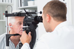 Optician examining senior patients eyes through slit lamp Stock Photography