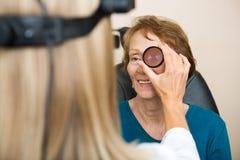 Optician Examining Senior Woman's Eye. Female optician examining senior woman's eye with binocular indirect ophthalmoscope stock photos