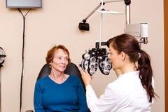 Optician explaining tests to senior Stock Image