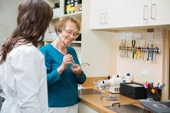 Optician With Female Apprentice Repairing Glasses Royalty Free Stock Photography