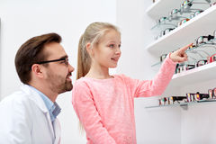 Optician and girl choosing glasses at optics store. Health care, people, eyesight and vision concept - optician and smiling girl choosing glasses at optics store Royalty Free Stock Images