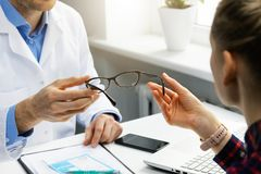 Optician gives new glasses to a patient. At office royalty free stock photo
