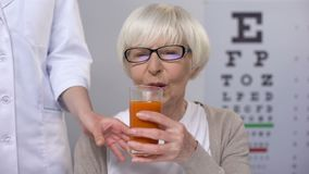 Optician giving fresh carrot juice to happy aged lady, maintaining good vision. Stock footage stock video