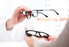 Optician giving new glasses to customer for testing and trying. Eye doctor showing patient lenses in spectacles store. Professional optometrist in white coat stock photography