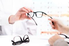 Optician giving new glasses to customer for testing and trying. Eye doctor with client comparing spectacles and choosing lenses in store Stock Photos