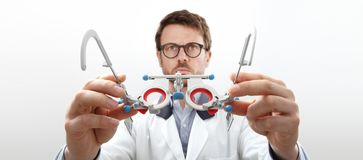 Optician hands with trial frame, optometrist doctor examines eye. Sight, front view  on white Royalty Free Stock Photo