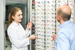 Optician helping client to choose spectacles Royalty Free Stock Photo