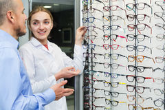Optician helping client to choose spectacles Stock Photo