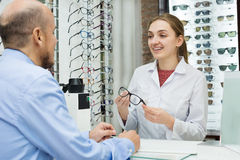 Optician helping client to choose spectacles Royalty Free Stock Photography