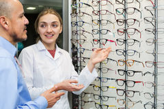 Optician helping client to choose spectacles. Professional female optician helping senior male client to choose spectacles Royalty Free Stock Photos