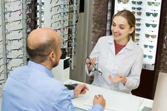 Optician helping client to choose spectacles Royalty Free Stock Photos