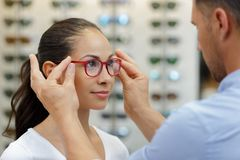 Optician helping client to fit eyeglasses stock photography