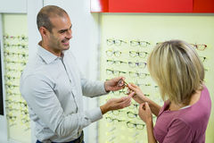 Optician helping customer for selecting a spectacles frame Stock Photos