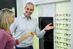 Optician helping customer for selecting a spectacles frame Royalty Free Stock Image