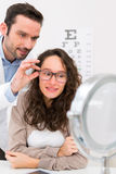 Optician helping out a woman to choose glasses Stock Photos