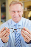Optician holding glasses at Stock Photos