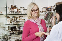 Optician holding mirror while senior female customer looking Royalty Free Stock Photos